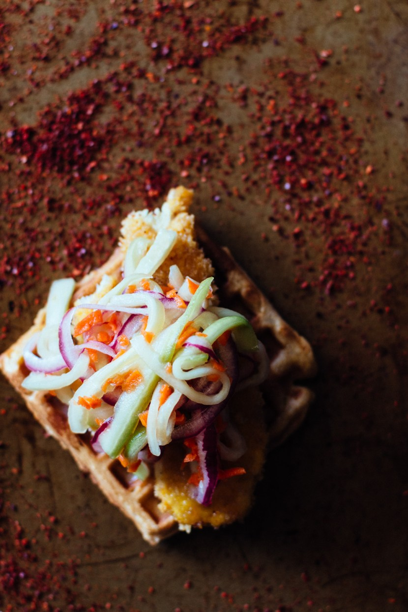 Overhead shot of a waffle topped with chicken tenders and pickled veggies on top of a pepper powder covered baking sheet.