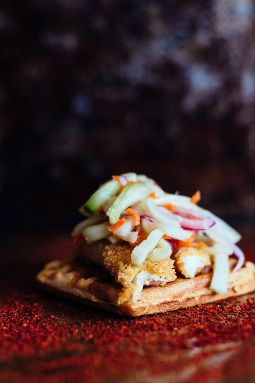 Vertical closer up shot of a waffle topped with chicken tenders and pickled veggies on top of a pepper powder covered baking skeet.