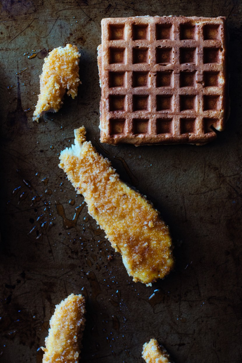 Overhead shot of a waffle on a baking sheet surrounded by chicken tenders.