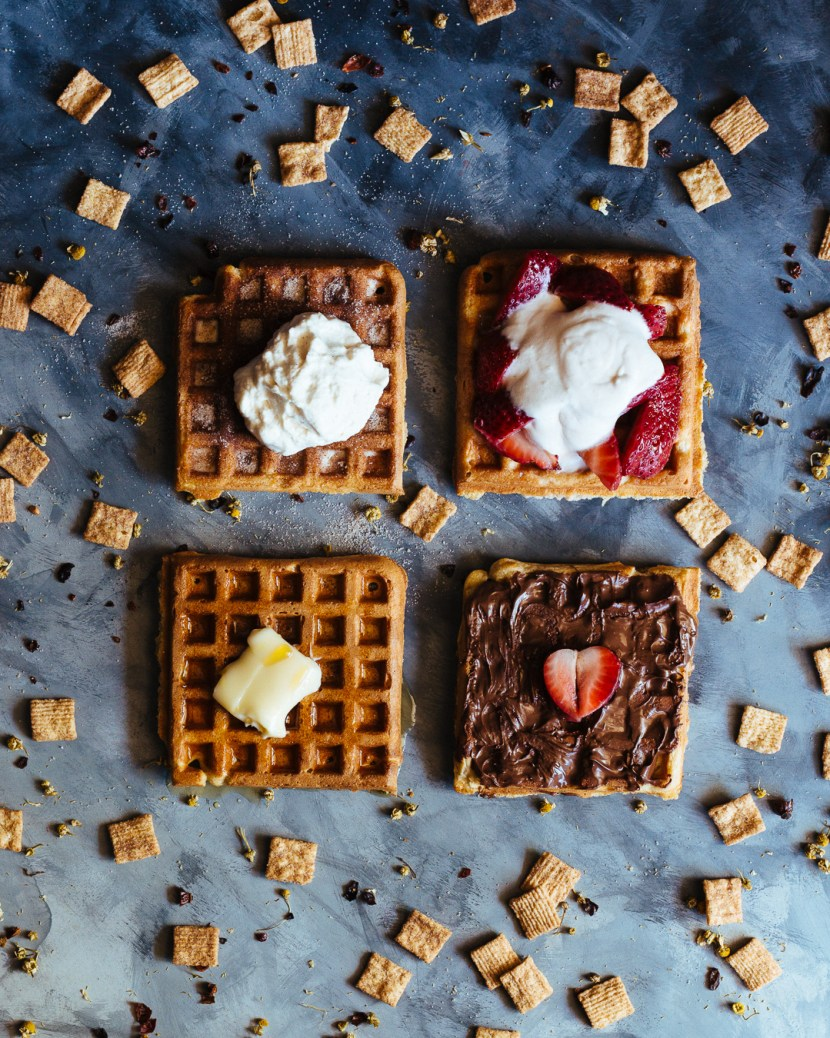 Overhead shot of four waffles with different toppings on them and surrounded by cinnamon toast crunch cereal.