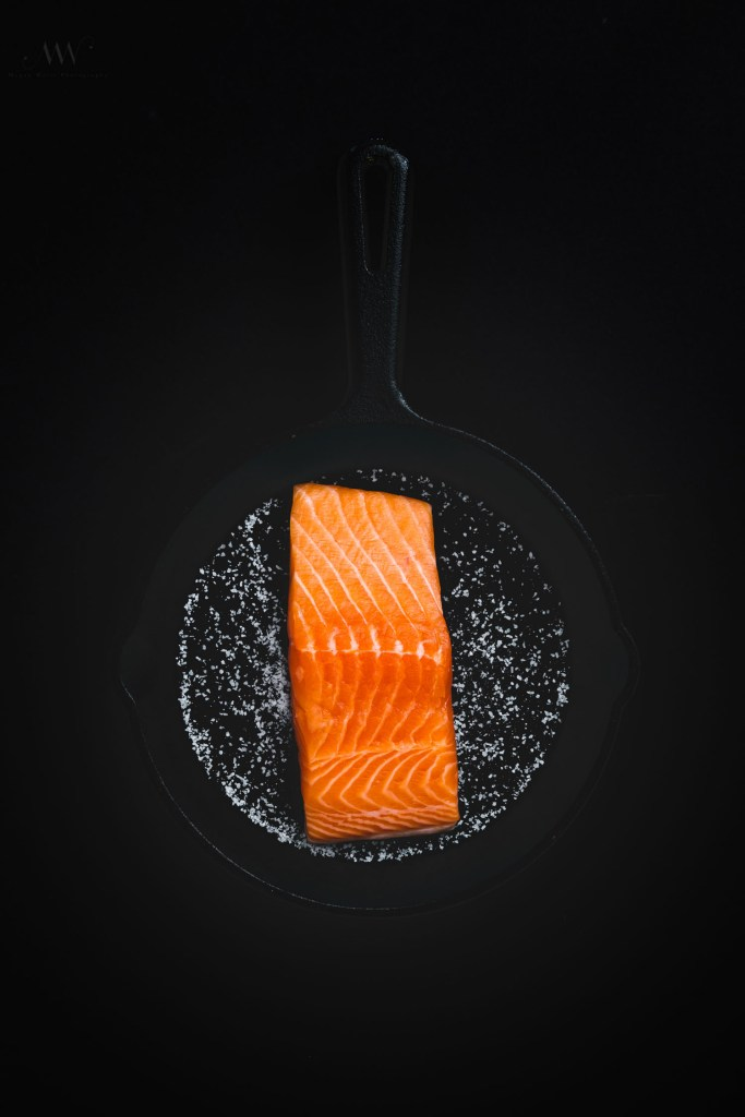 Overhead shot of raw salmon skin side down on a cast iron skillet covered with salt.