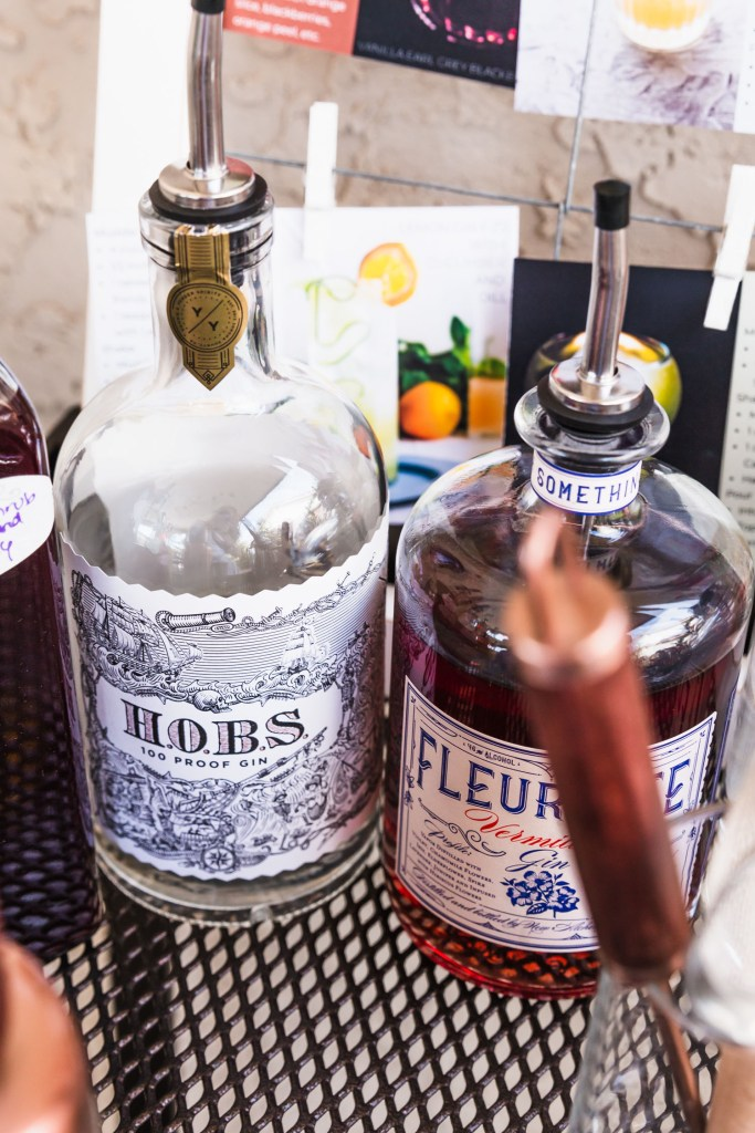 Vertical side shot of Young and Yonder H.O.B.S. Gin surrounded by other gins and bar tending tools.