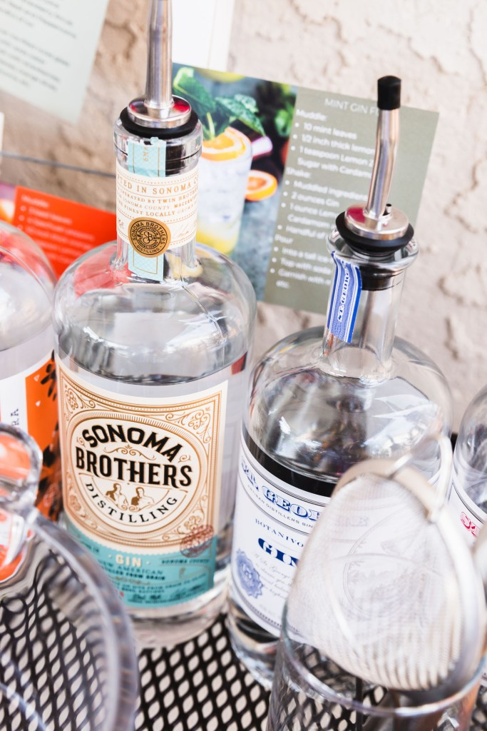 Vertical shot of a bottle of Sonoma Brothers Gin surrounded by other bottles of gin and bar tending tools.