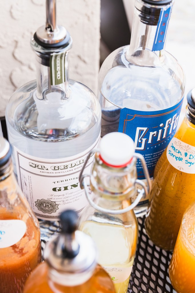 Vertical side shot of St. George Spirits Terroir Gin surrounded by other gin bottles and bottled syrups and juices.