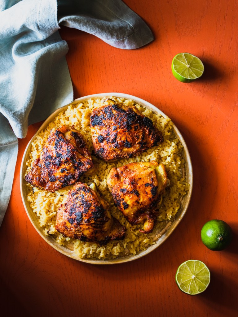 Overhead shot of rice topped with chicken thighs on a platter surrounded by limes and a napkin.