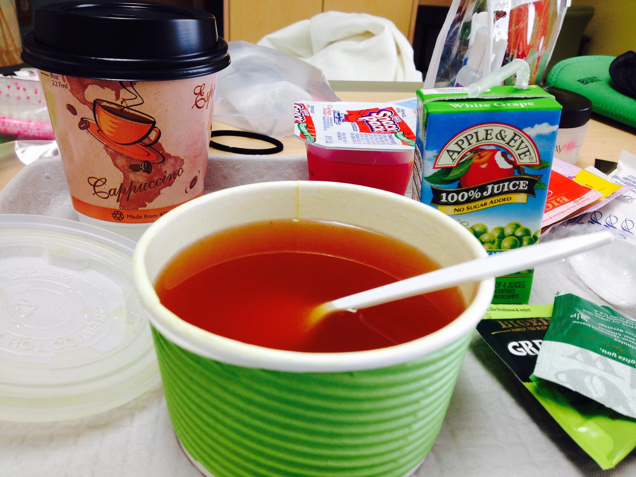 Picture of broth in a take away container, a box of apple juice, jello, and a to-go coffee cup from my first hospitalization.