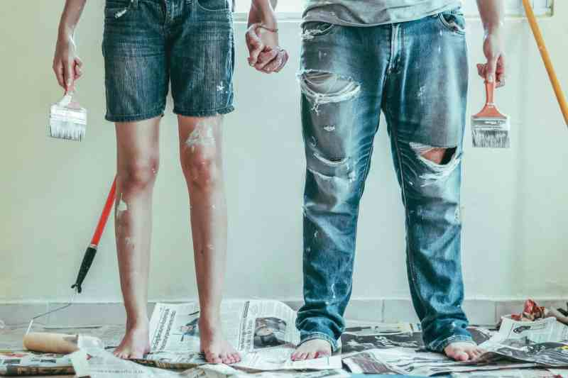 Couple surrounded by paint and brushes