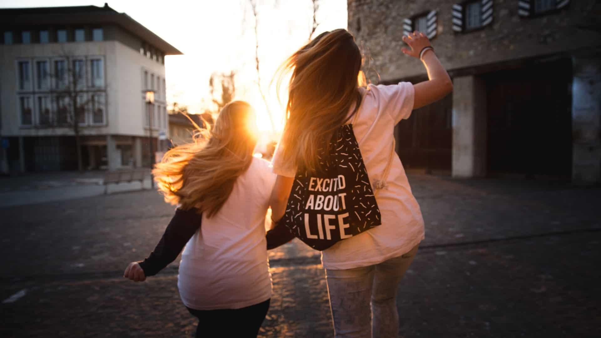 2 women walking across a road