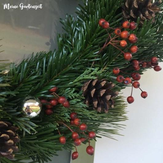 Weihnachtlicher Kranz aus Zweigen, Perlhagebutten, Zapfen und Christbaumkugeln