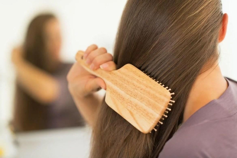 Mujer cepillándose el cabello.