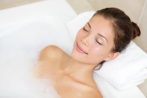 Mujer sumergida en la bañera con espuma.