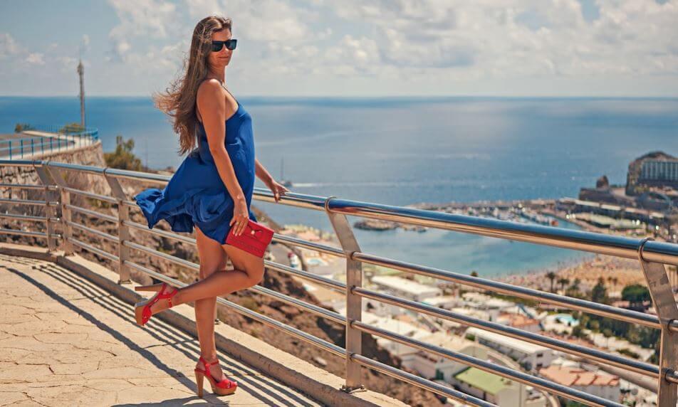 Chica posa con un vestido azul y zapatos de tacón rojos.