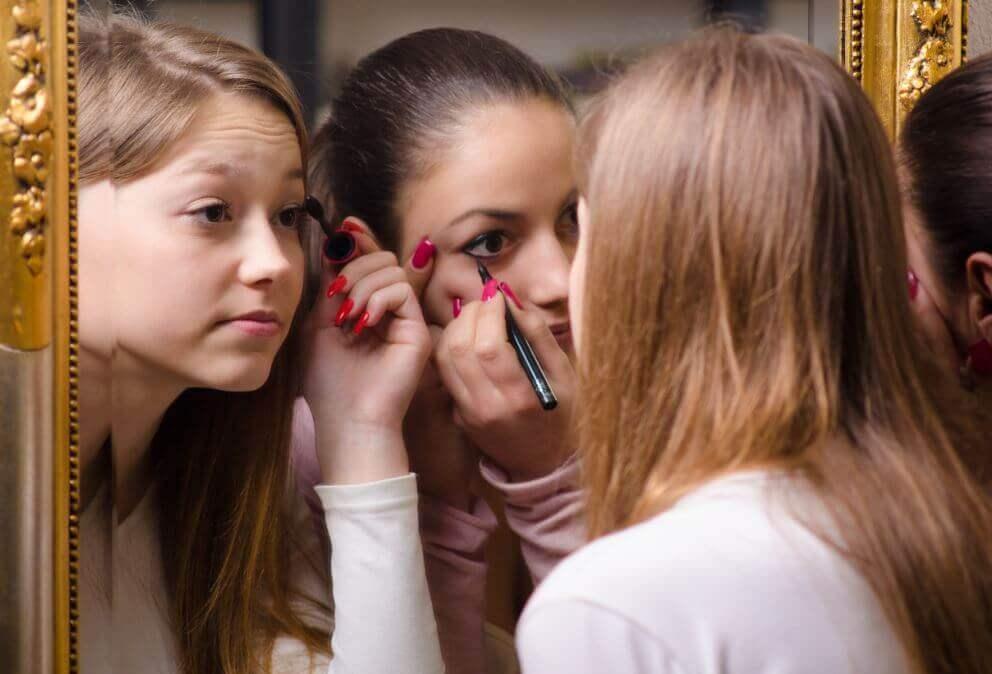 Chicas maquillándose los ojos frente a un espejo.