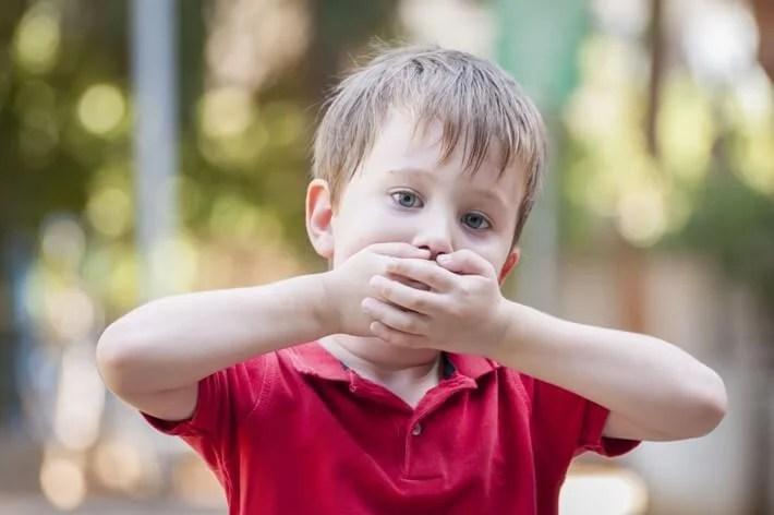 Niño tapándose la boca.