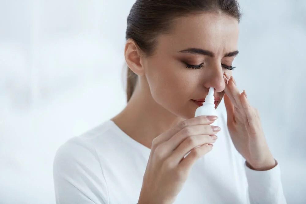 Mujer aplicándose un spray nasal