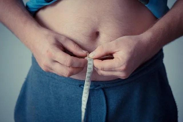 Un uomo che misura il suo grasso corporeo