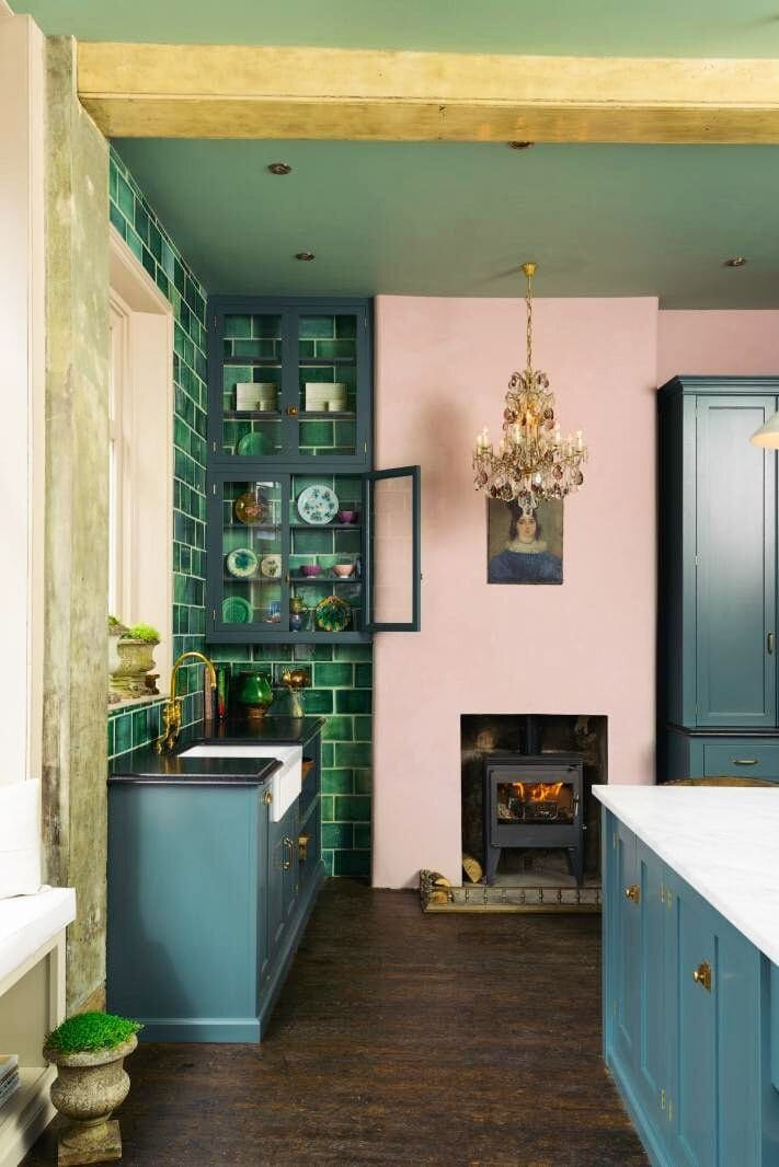Green tiles and a pink chimney breast provide a stunning contrast in this kitchen. Credit: @devolkitchens