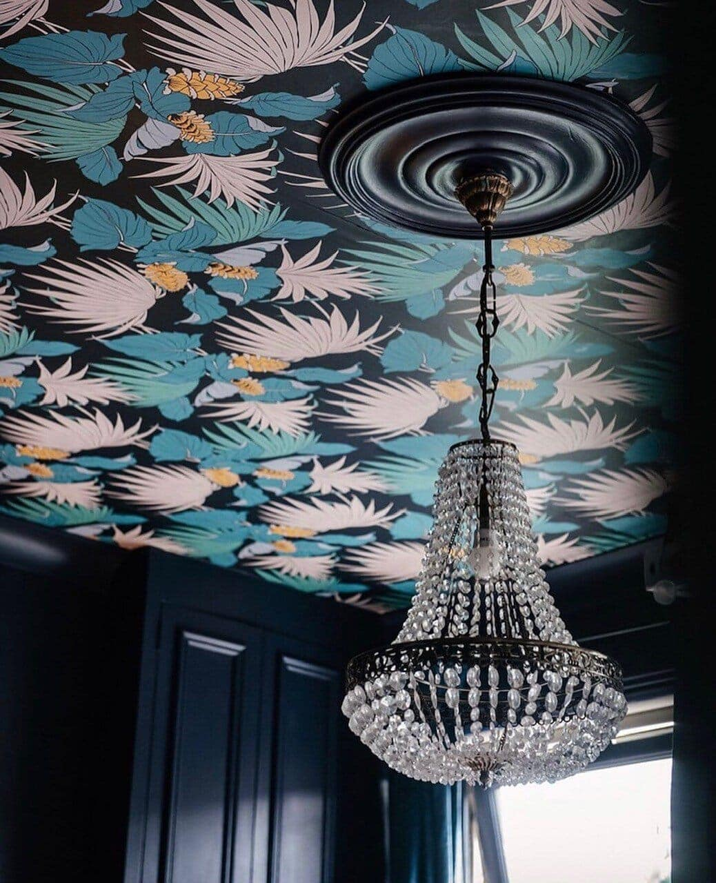 The chandelier adds a touch of glamour and contrast to the whimsical wallpaper