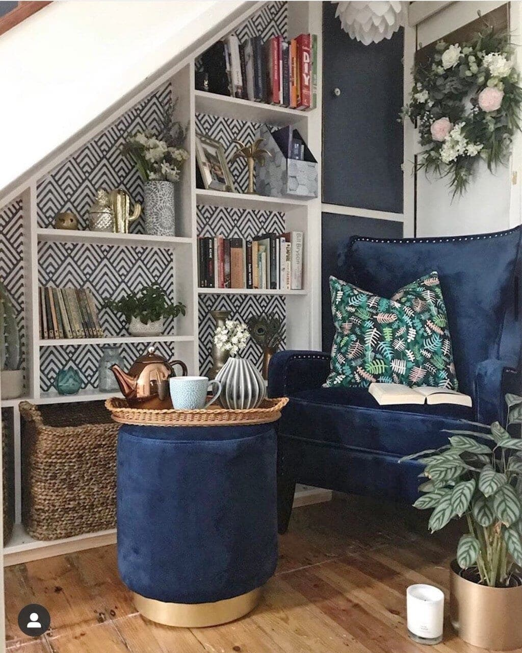 Adding this geometric wallpaper to the back of the shelves and a patterned cushion has broken up the block of colour and transformed this space.