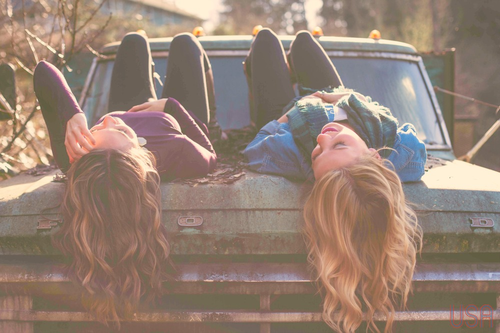when you've got the blues, two women laying on hood of old Ford truck laughing