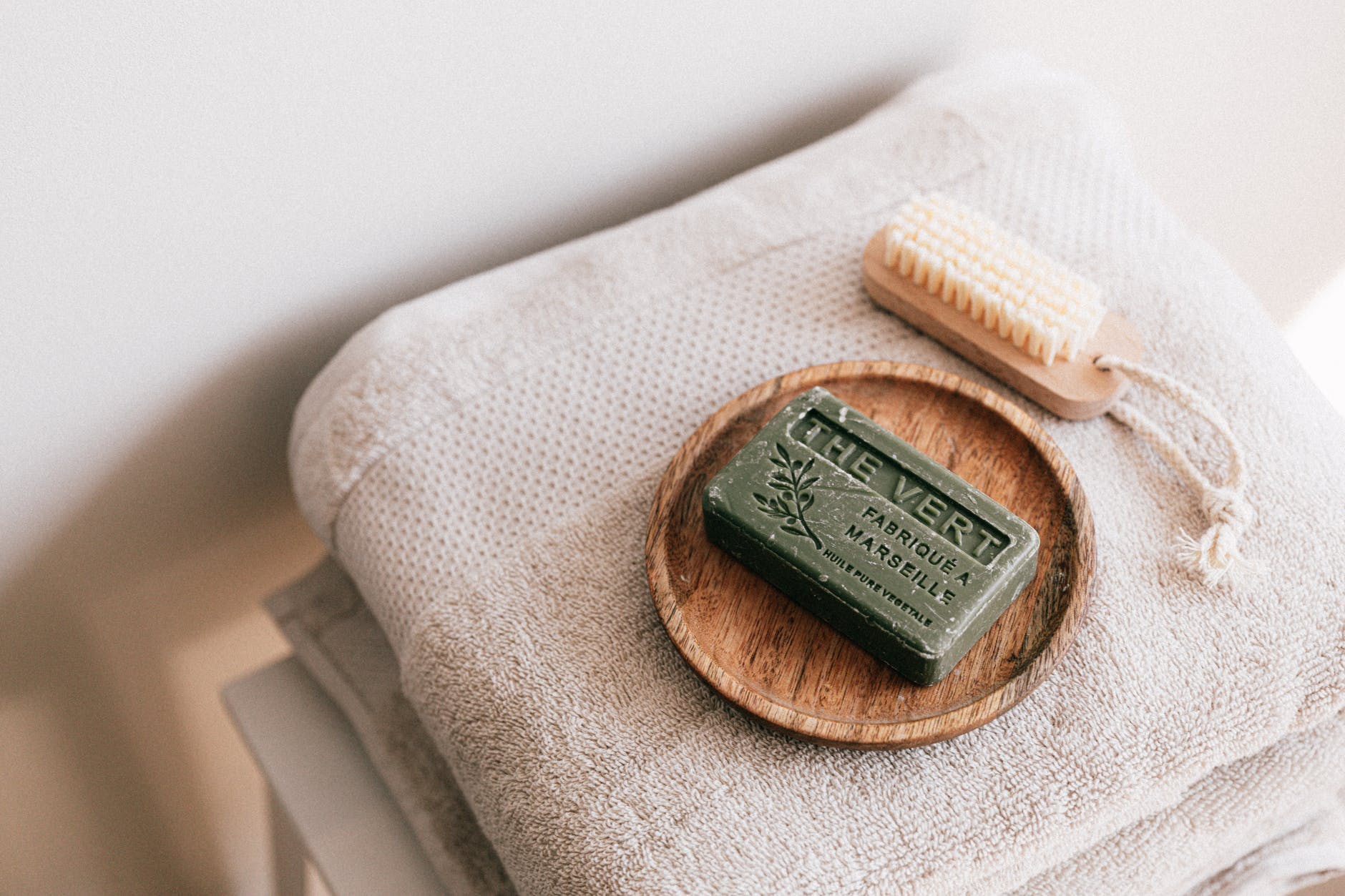 natural soap and brush on folded towels