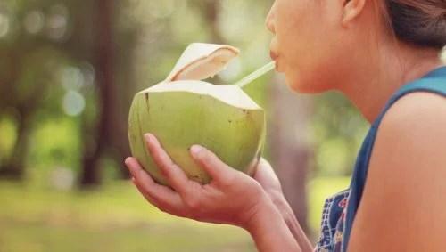 Mulher tomando água de coco