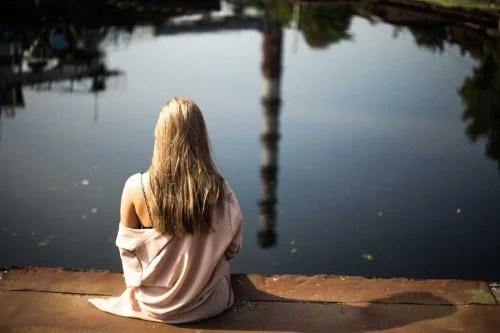 Mulher relaxando diante de lago