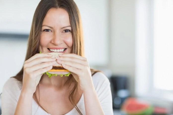 mulher-comendo-sanduiche 5 cafés da manhã saudáveis para começar o seu dia com energia