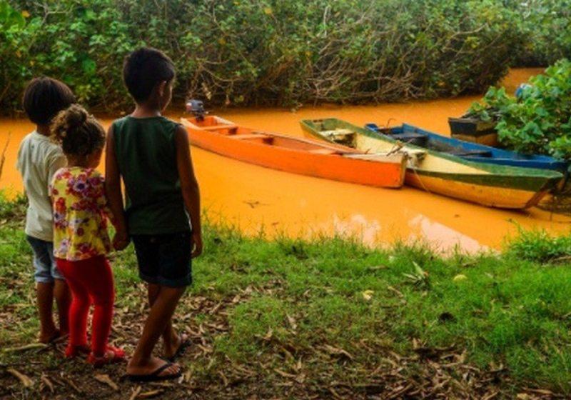 Crianças observam a lama tomando um braço do manguezal em Regência (ES): futuro ameaçado