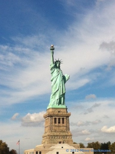 """The ferry to Ellis Island first stops at Llberty Island. Here you will see the Statue of Liberty, constructed in Paris, France in the 1880s and proclaimed as the """"Eighth marvel of the world."""" From ground to the top of the torch, she is 305 feet, 1 inch tall. And she is OH so glorious!"""