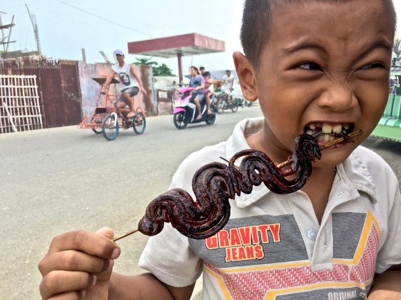 Filipino boy eating a BBQ stick of eels