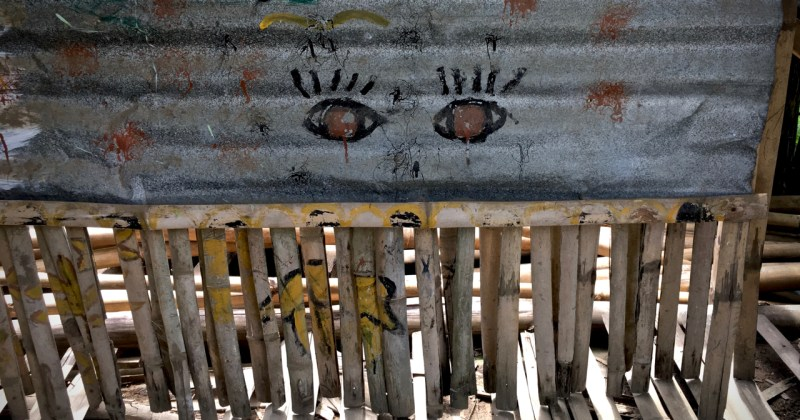 pair of eyes painted onto a corrugated iron and bamboo shack