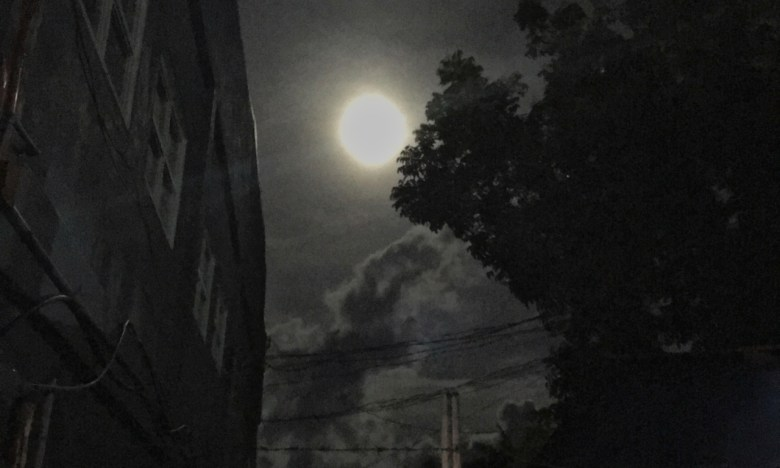 full moon shining over an alley and barbed wire
