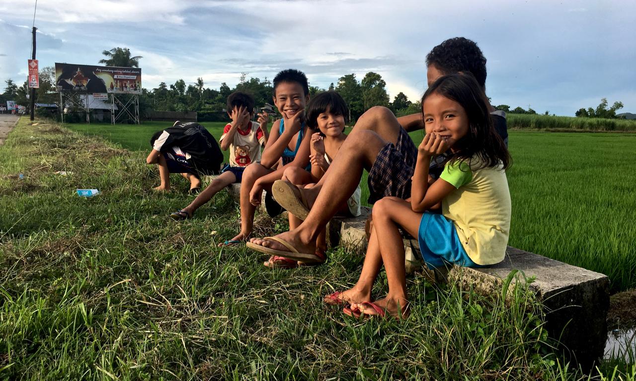 group of Filipino kids sitting on a little bridge