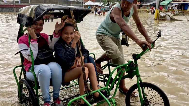 group of girls in floodwaters from Urduja, balasan philippines