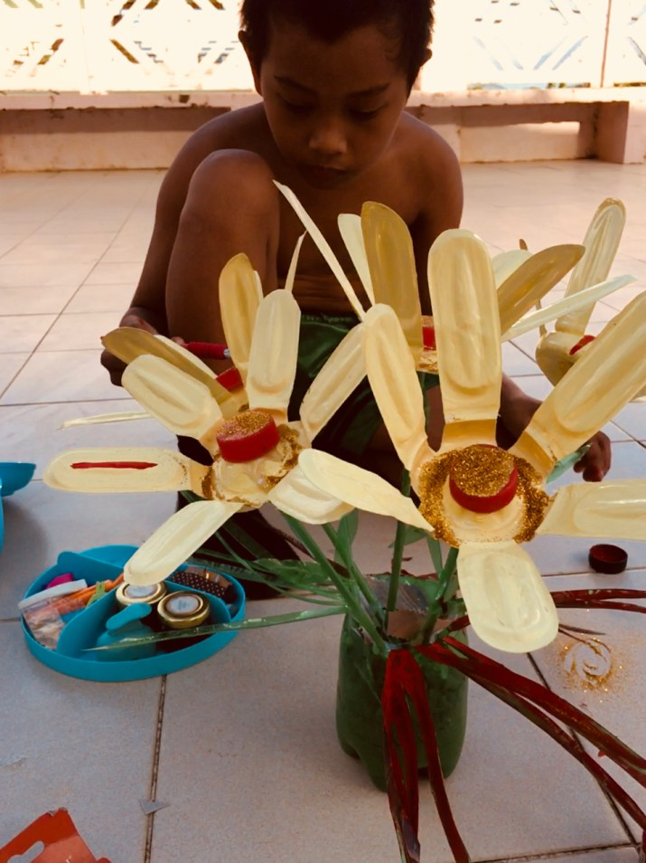 little boy painting plastic flowers