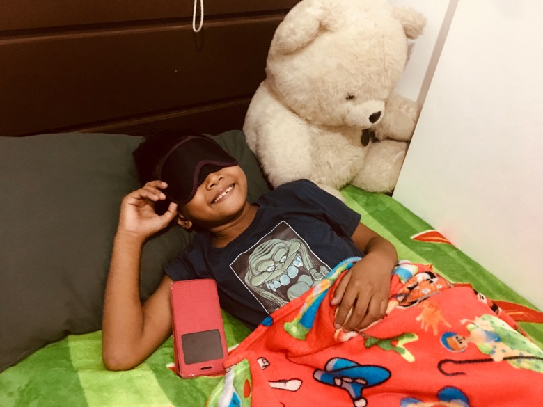a boy wearing bat mask in bed with teddy bear