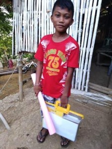 Filipino boy holding school supplies