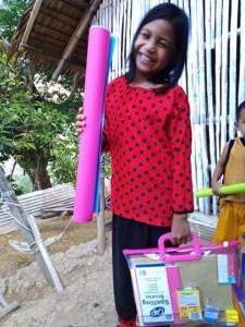 Filipino girl holding school supplies