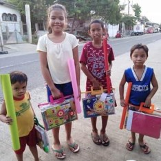 group of Filipino kids with school supplies