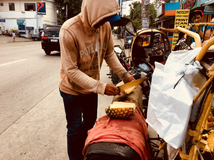 young man cuts pineapples on the streets of the Philippines