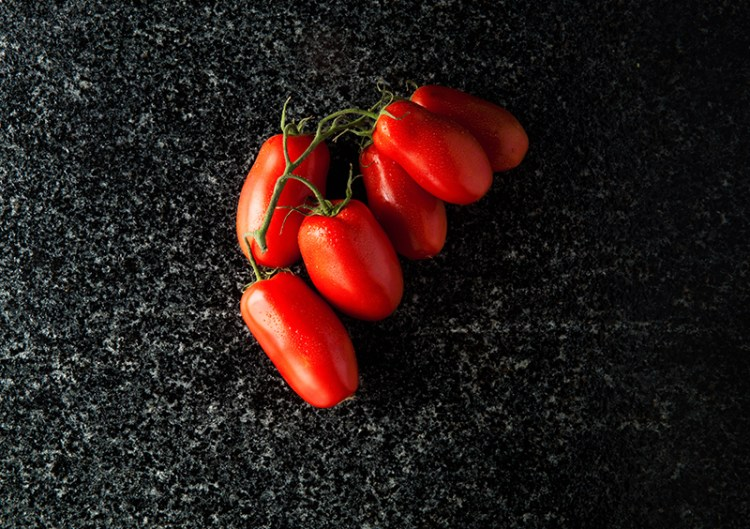 ripe tomatoes on black marble