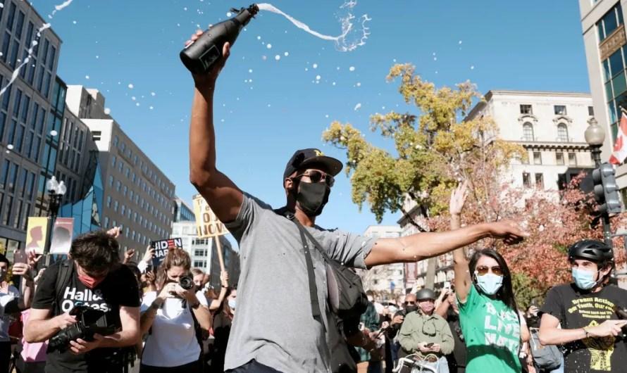 Biden Supporters drink champagne from bottles in celebration