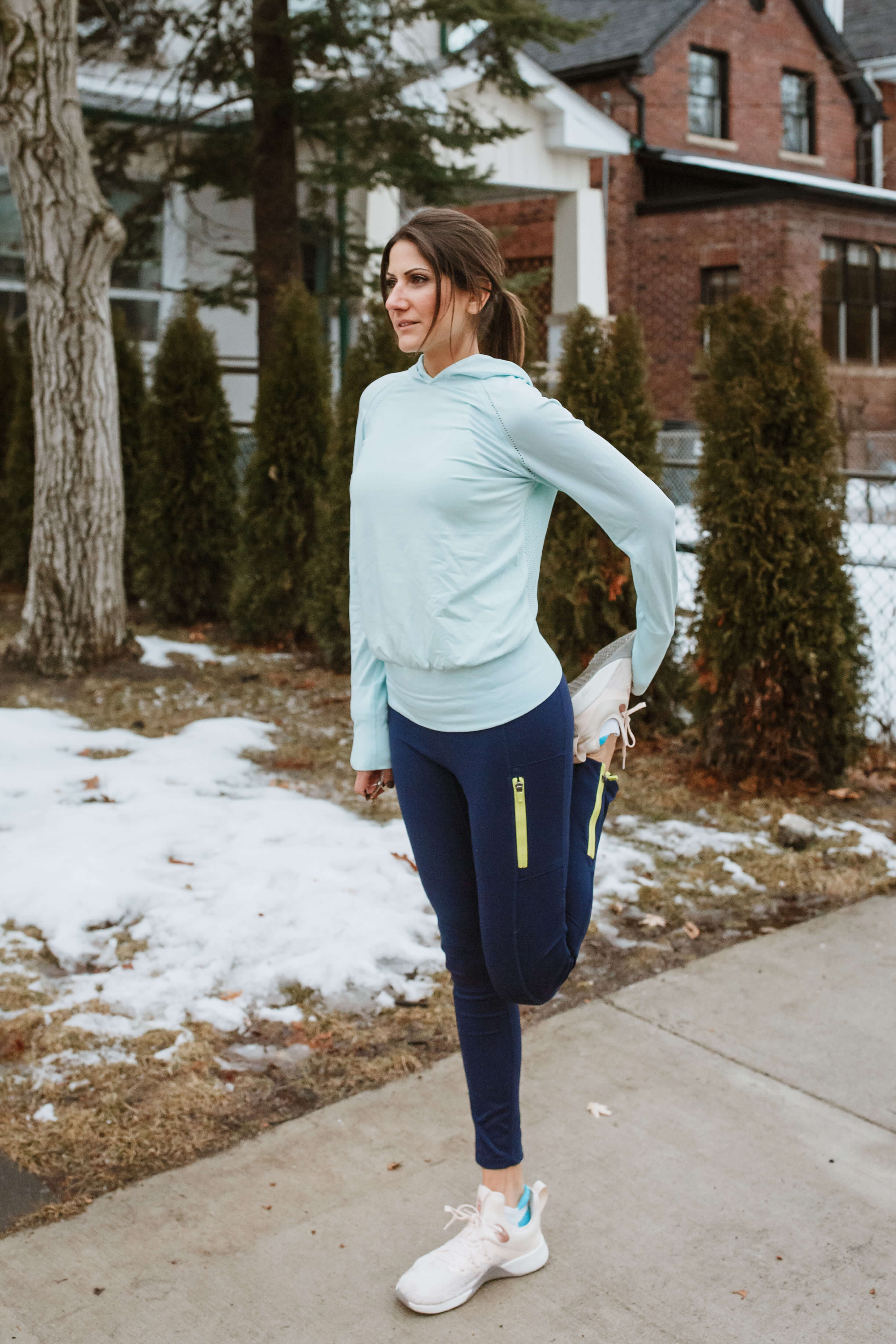MellyFit Nutrition womon ni a blue sweater and navy blue jogging pants doing a left leg stretch