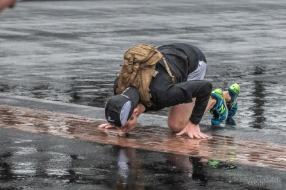 A runner stops to kiss the Yard of Bricks as per race tradition on the lap around the Indianapolis Motor Speedway despite the rain during the Annual OneAmerica 500 Festival Mini-Marathon on Saturday, May 4, 2019.