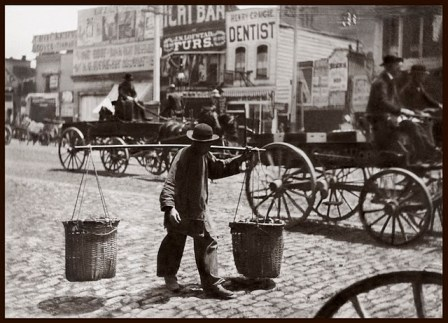 A Chinese labourer carries wicker baskets on a pole. In the background, wagons and businesses are visible.