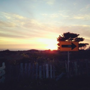The sun setting over Mendocino, with a directional arrow sign in the foreground.