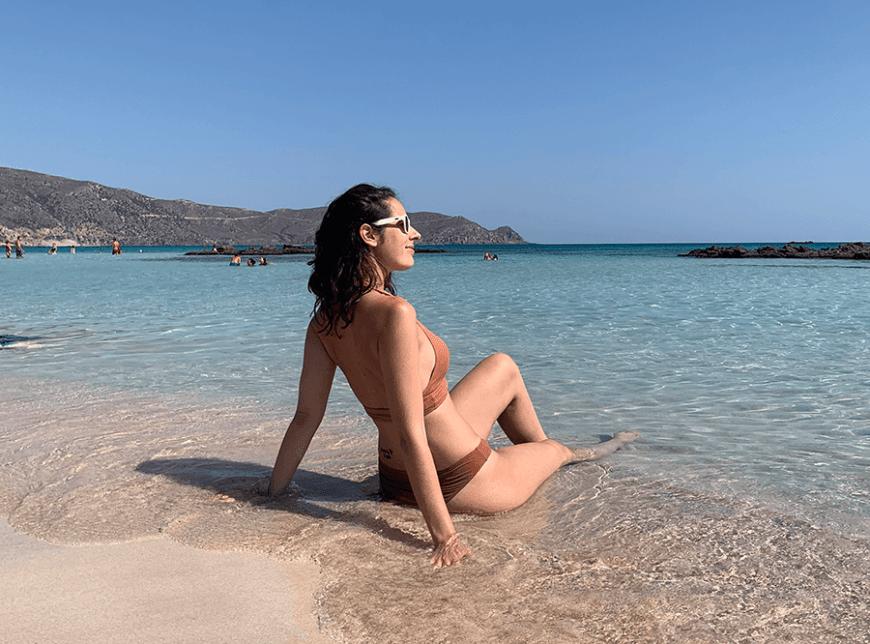 chica tomando el sol en playa elafonisi en isla de creta