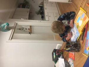 An image of a child completing a page of the baby + me book, a book for older siblings. baby + me is in a unique format, with space for the child to write and to draw