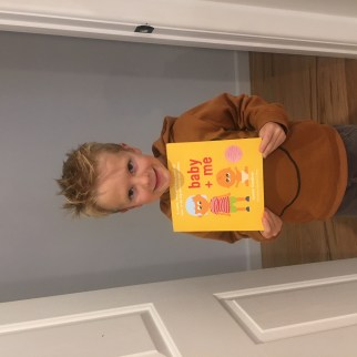 Picture of a child holding baby + me, a new sibling book!